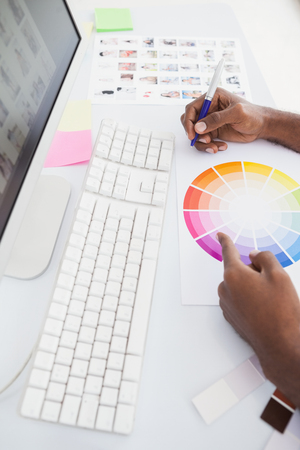 colour wheel: Businessman working with colour wheel and taking notes in the office