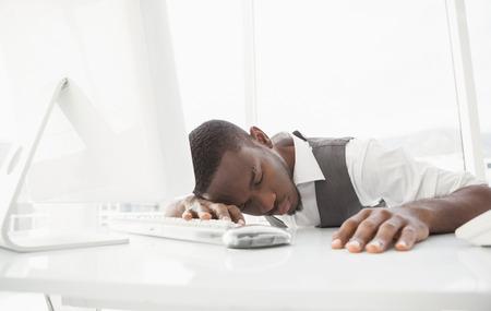 slumped: Tired businessman sleeping on keyboard in his office