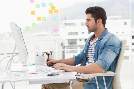 usando computadora: Diseñador concentrado usando la computadora y digitalizador en la oficina