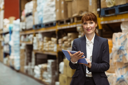 scrolling: Smiling businesswoman scrolling on digital tablet in a large warehouse