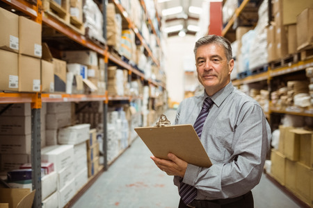 warehouses: Smiling warehouse manager holding a clipboard in a large warehouse
