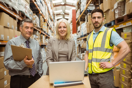 organised: Smiling warehouse team working together on laptop in a large warehouse Stock Photo