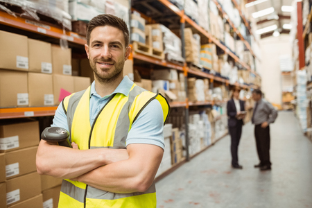 Smiling worker standing with arms crossed in a large warehouse Archivio Fotografico