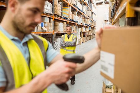 Magazijnmedewerker scannen barcode op doos in een groot magazijn Stockfoto
