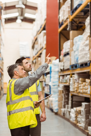 warehouse: Warehouse manager talking with worker in a large warehouse Stock Photo