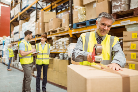 sealing: Warehouse worker sealing cardboard boxes for shipping in a large warehouse Stock Photo