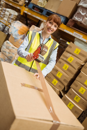 sealing tape: Smiling warehouse workers preparing a shipment in a large warehouse