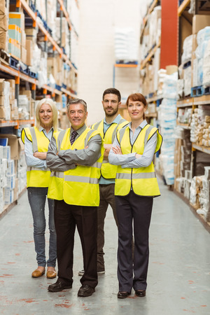 warehouse: Smiling warehouse team with arms crossed in a large warehouse