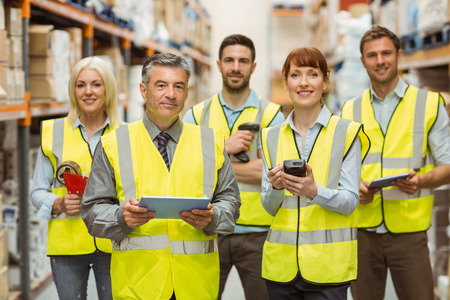hand held computer: Smiling warehouse team looking at camera in a large warehouse