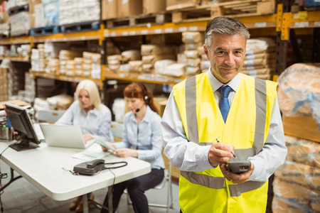 hand held computer: Smiling manager wearing yellow vest using handheld in a large warehouse Stock Photo