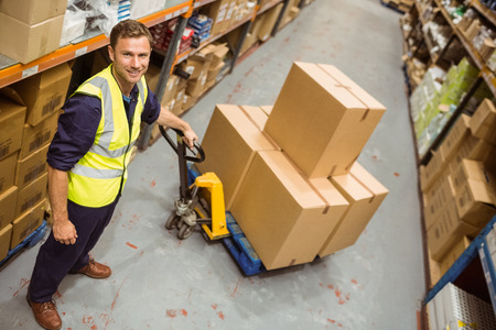 warehouse: Worker with trolley of boxes smiling at camera in a large warehouse Stock Photo