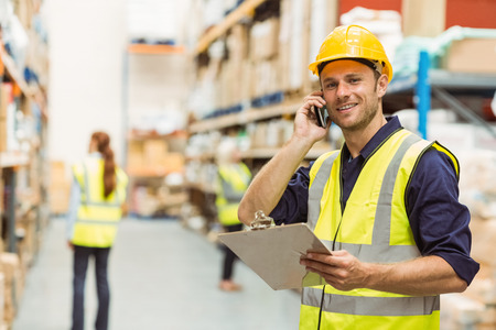 interaction: Warehouse worker talking on the phone holding clipboard in a large warehouse