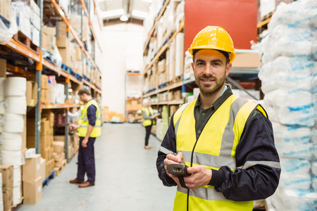 hand held computer: Smiling worker wearing yellow vest using handheld in a large warehouse