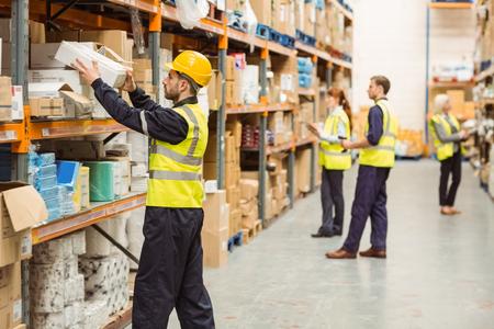 worker: Trabajador del almacén teniendo paquete en el estante en un gran almacén en un gran almacén