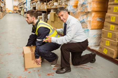manual job: Manager training worker for health and safety measure in a large warehouse Stock Photo