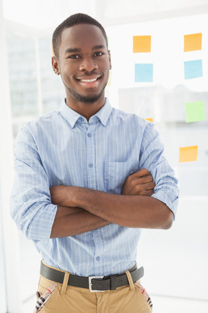 career young: Smiling businessman standing with arms crossed in the office