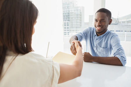 male hands: Handshake to seal a deal after a business meeting in the office Stock Photo