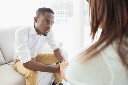 young adult men: Therapist advising his listening patient at therapy session