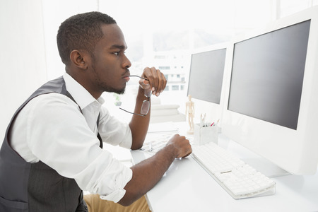 Focused businessman holding glasses and using computer in the office