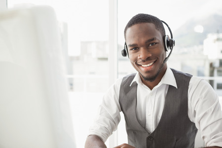 Happy businessman with headset interacting in his office Stockfoto