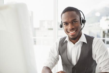 hombres negros: Hombre de negocios feliz con auriculares interactuando en su oficina