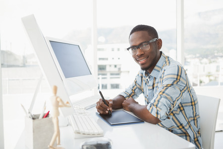 digitizer: Smiling businessman using digitizer at desk in the office