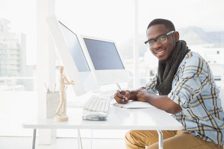 hombres de negro: hombre de negocios tomando notas ocasional feliz en la oficina