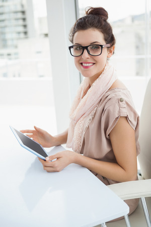 causal: Smiling causal businesswoman using tablet in the office Stock Photo