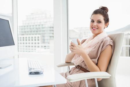 relajado: Empresaria Relaxed que sostiene una bebida caliente en la oficina Foto de archivo