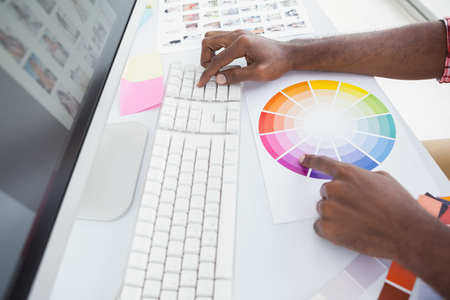 colour wheel: Designer using a colour wheel and typing on keyboard in the office
