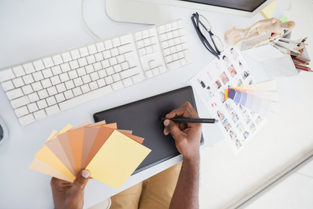 digitizer: Designer using digitizer and colour wheel in the office Stock Photo