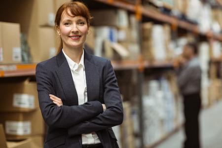 gerente: Encargado de sexo femenino con los brazos cruzados en un gran almac�n