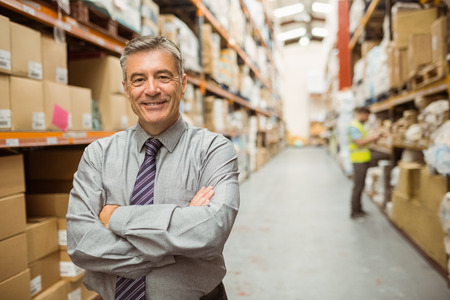 Smiling businessman with crossed arms in a large warehouse Archivio Fotografico