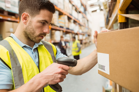 codigos de barra: Trabajador del almacén escanear códigos de barras en las cajas en un almacén grande