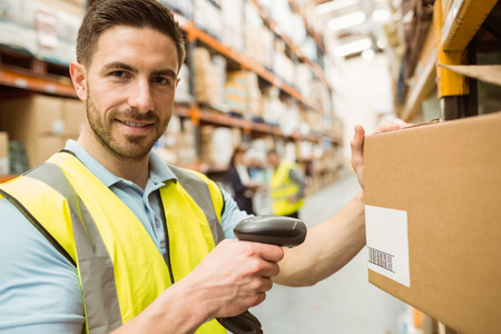 barcode scanning: Warehouse worker scanning box while smiling at camera in a large warehouse