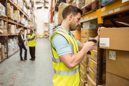 mujer trabajadora: Trabajador del almacén de escaneo de código de barras en la caja en un gran almacén Foto de archivo