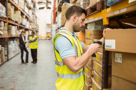 Warehouse worker scanning barcode on box in a large warehouse Banco de Imagens