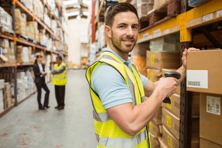 the pallet: Almac�n cuadro de escaneo trabajador mientras sonriendo a la c�mara en un gran almac�n Foto de archivo
