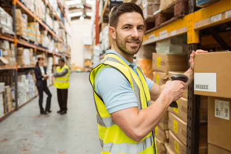 Warehouse worker scanning box while smiling at camera in a large warehouse 版權商用圖片 - 36345222