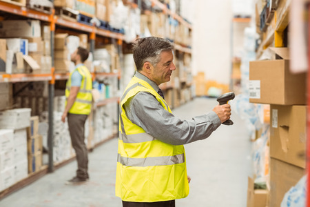 Warehouse worker scanning barcode on box in a large warehouse Stok Fotoğraf
