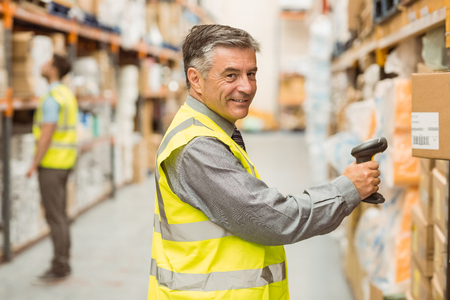 hombres trabajando: Warehouse worker scanning barcode on box in a large warehouse Foto de archivo