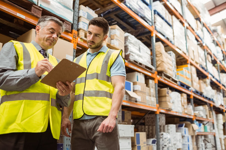 manual worker: Warehouse manager speaking with foreman in a large warehouse