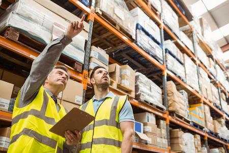 the pallet: El gerente de almac�n y capataz trabajando juntos en un gran almac�n