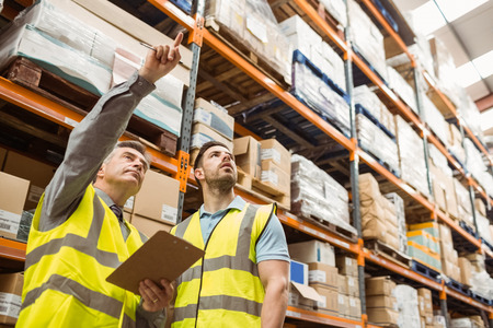 shipment: Warehouse manager and foreman working together in a large warehouse
