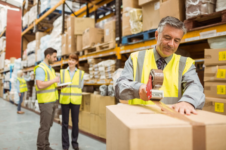 shipping: Warehouse worker sealing cardboard boxes for shipping in a large warehouse Stock Photo
