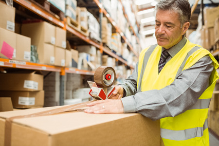 sealing tape: Warehouse worker sealing cardboard boxes for shipping in a large warehouse Stock Photo