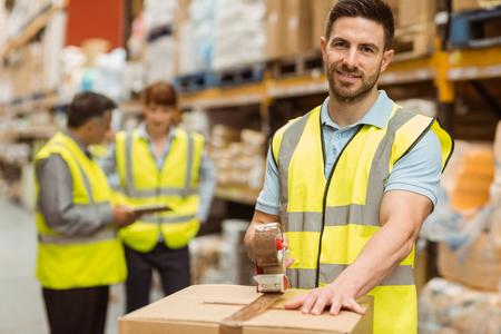 operarios trabajando: Sonriendo trabajadores del almacén preparando un envío en un gran almacén