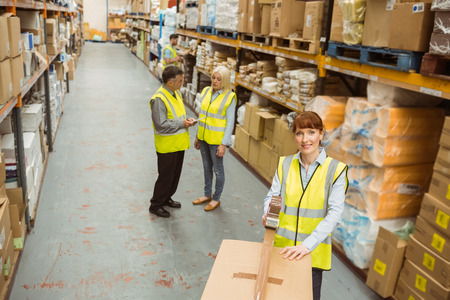 female worker: Warehouse worker sealing cardboard boxes for shipping in a large warehouse Stock Photo