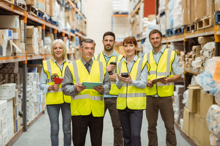warehouse: Smiling warehouse team looking at camera in a large warehouse