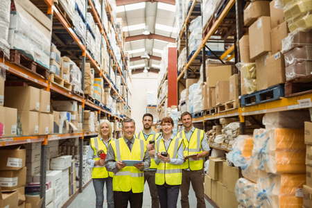 Smiling warehouse team looking at camera in a large warehouse photo